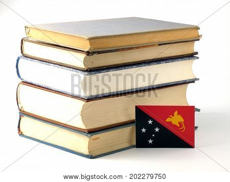 Papua New Guinea Flag With Pile Of Books Isolated On White Background