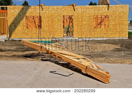 Pre-built rafters(trusses) are being lifted by a cable and boom to be placed on top of a wooden framed building under construction.