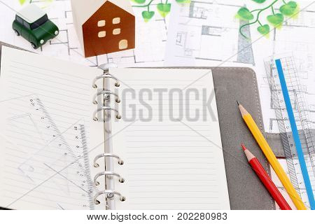 miniature model of house and opened notebook on blueprints