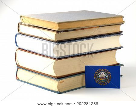 New Hampshire Flag With Pile Of Books Isolated On White Background