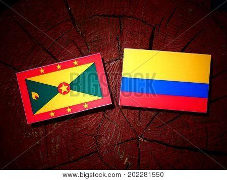 Grenada Flag With Colombian Flag On A Tree Stump Isolated
