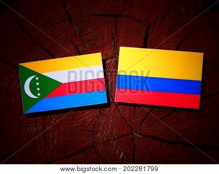 Comoros Flag With Colombian Flag On A Tree Stump Isolated