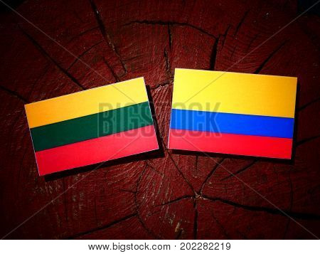 Lithuanian Flag With Colombian Flag On A Tree Stump Isolated