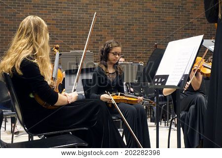 ROMEOVILLE, ILLINOIS / UNITED STATES - OCTOBER 26, 2016: Violinists of the Metropolitan Youth Symphony Orchestra (MYSO) sit on the stage, with their instruments, prior to a concert in Borromeo Hall at Lewis University.
