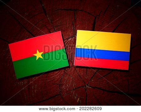 Burkina Faso Flag With Colombian Flag On A Tree Stump Isolated