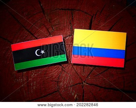Libyan Flag With Colombian Flag On A Tree Stump Isolated