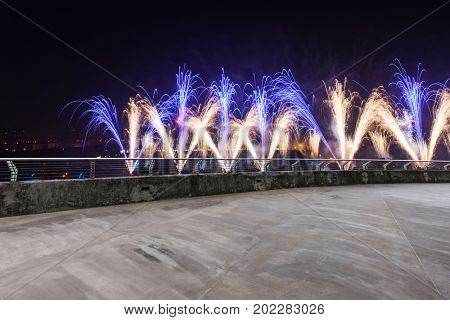 empty concrete road and cityscape of hangzhou with fireworks at night