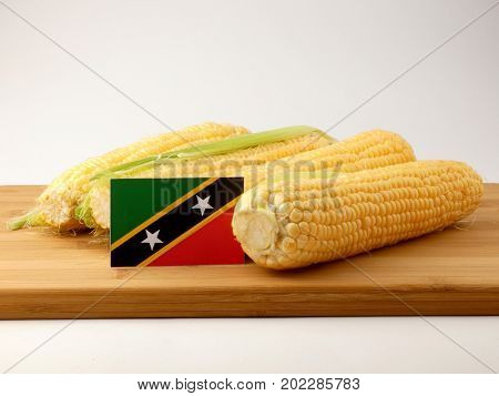 Saint Kitts And Nevis Flag On A Wooden Panel With Corn Isolated On A White Background