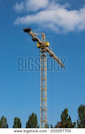 Yellow building crane against blue sky in summer