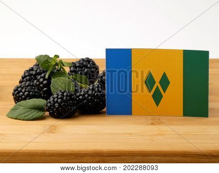 Saint Vincent And The Grenadines Flag On A Wooden Panel With Blackberries Isolated On A White Backgr