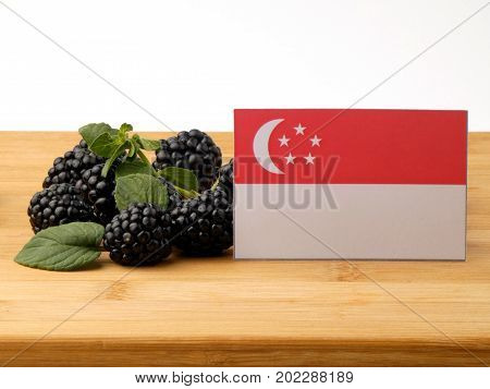 Singaporean Flag On A Wooden Panel With Blackberries Isolated On A White Background