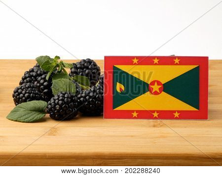 Grenada Flag On A Wooden Panel With Blackberries Isolated On A White Background