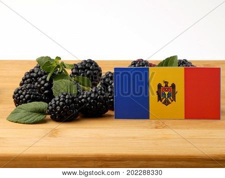 Moldovan Flag On A Wooden Panel With Blackberries Isolated On A White Background
