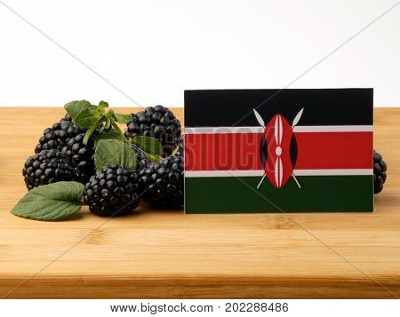Kenyan Flag On A Wooden Panel With Blackberries Isolated On A White Background