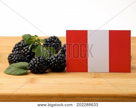 Peruvian Flag On A Wooden Panel With Blackberries Isolated On A White Background