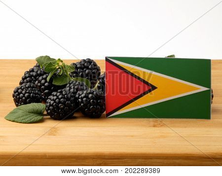 Guyana Flag On A Wooden Panel With Blackberries Isolated On A White Background