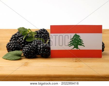 Lebanese Flag On A Wooden Panel With Blackberries Isolated On A White Background