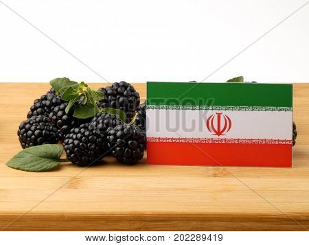Iranian Flag On A Wooden Panel With Blackberries Isolated On A White Background