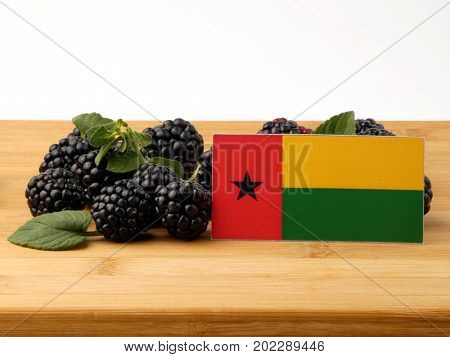 Guinea Bissau Flag On A Wooden Panel With Blackberries Isolated On A White Background
