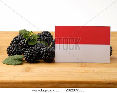 Indonesian Flag On A Wooden Panel With Blackberries Isolated On A White Background