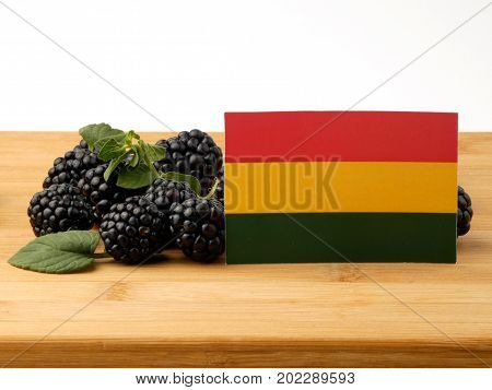 Bolivian Flag On A Wooden Panel With Blackberries Isolated On A White Background