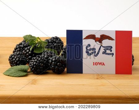 Iowa Flag On A Wooden Panel With Blackberries Isolated On A White Background