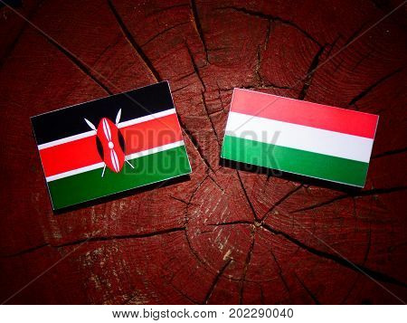 Kenyan Flag With Hungarian Flag On A Tree Stump Isolated