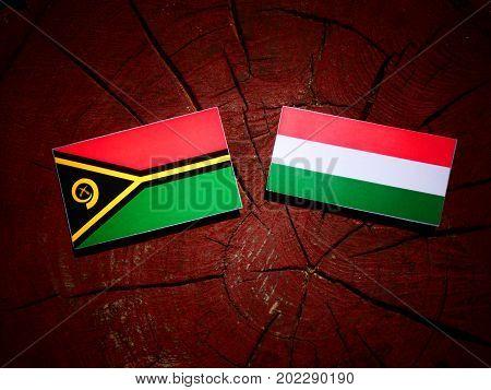 Vanuatu Flag With Hungarian Flag On A Tree Stump Isolated