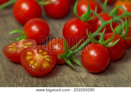 Fresh cherry tomato on rustic wood table. Close up lovely cherry tomato for background or wallpaper. Prepare fresh cut cherry tomato for home cooking look so delicious. Macro concept with copy space.Cherry tomato in fresh vegetable concept.