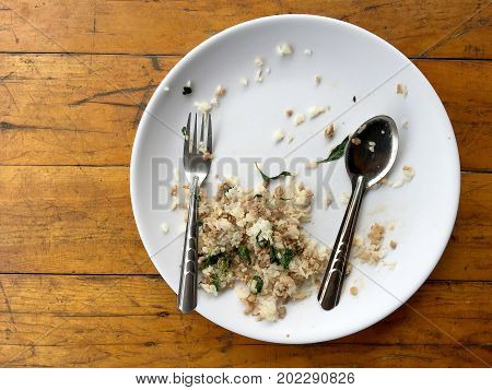 Empty Dish With Spoon And Fork After Eating On The Wooden Table. Top View Of Empty Plate, Dirty Afte