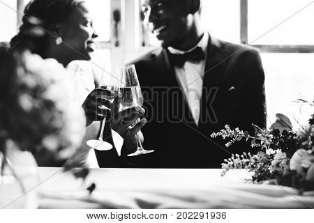 African Descent Bride and Groom Clinking Glasses Together