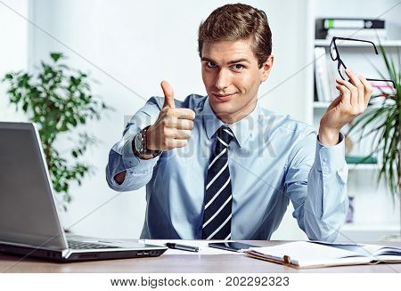 Successful businessman takes off his glasses and showing thumb up. Photo of young man working in the office. Business concept