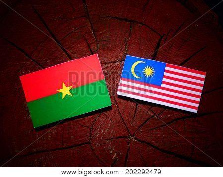 Burkina Faso Flag With Malaysian Flag On A Tree Stump Isolated