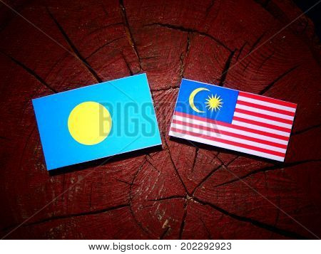 Palau flag with Malaysian flag on a tree stump isolated poster
