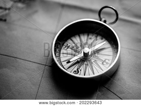 Closeup of metallic compass on the map journey planning grayscale
