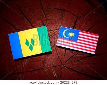 Saint Vincent And The Grenadines Flag With Malaysian Flag On A Tree Stump Isolated