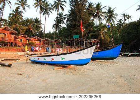 Two motor boats at the tropical beach with white sand. Fishing boat on the sand. Bright painted small fishing boat near beach house and bar