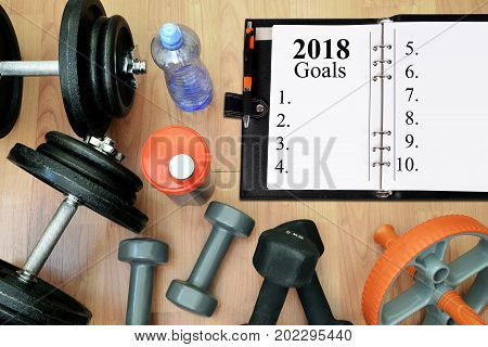Dumbbells with protein shake and open notebook on wooen desk. Healthy resolutions for the New Year 2018.