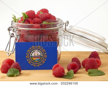 New Hampshire Flag On A Wooden Panel With Raspberries Isolated On A White Background