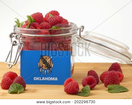 Oklahoma Flag On A Wooden Panel With Raspberries Isolated On A White Background