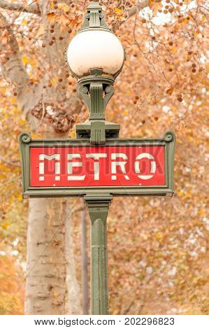 Parisian lamppost with metro sign in downtown in the fall, France