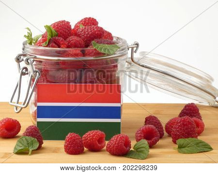 Gambia Flag On A Wooden Panel With Raspberries Isolated On A White Background