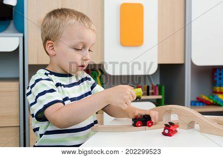 Child Boy Play With Wooden Train In Kindergarten