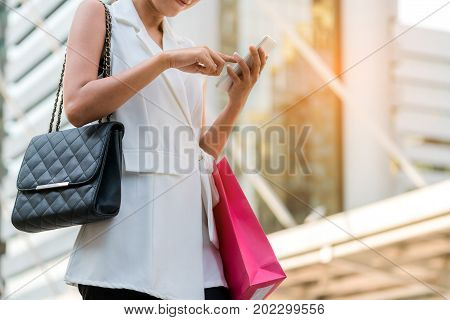 Happy Woman With Shopping Bag Using Mobile Phone