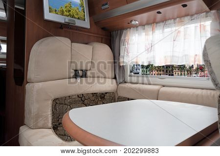Interior of a motorhome through the window overlooking the Mediterranean Sea and the port of Port Andratx on Mallorca.
