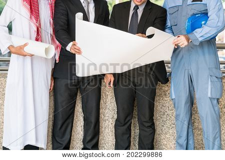 Engineer businessmen and Arab man meeting about construction drawing discussion. Multicultural oversea engineering business concept.