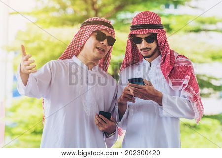 Arab Men Talking And Using Mobile Phone