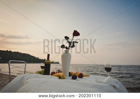 A Red Rose Stands In A Vase On A Table With Fruits, A Bottle Of Red Wine, A Glass On The Beach Near