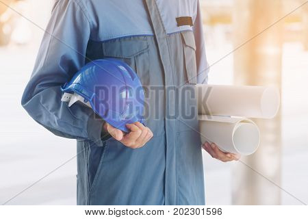 Engineer Holding Hard Hat And Blueprint