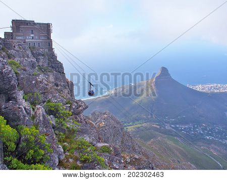 Cape Town, South Africa - September 12, 2016: The Table Mountain Cableway takes passengers to upper cable station on Table Mountain National Park in Cape Town, South Africa. Lion's Head as background.